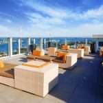 Roof deck with lounge chairs with a view of the water in the background.