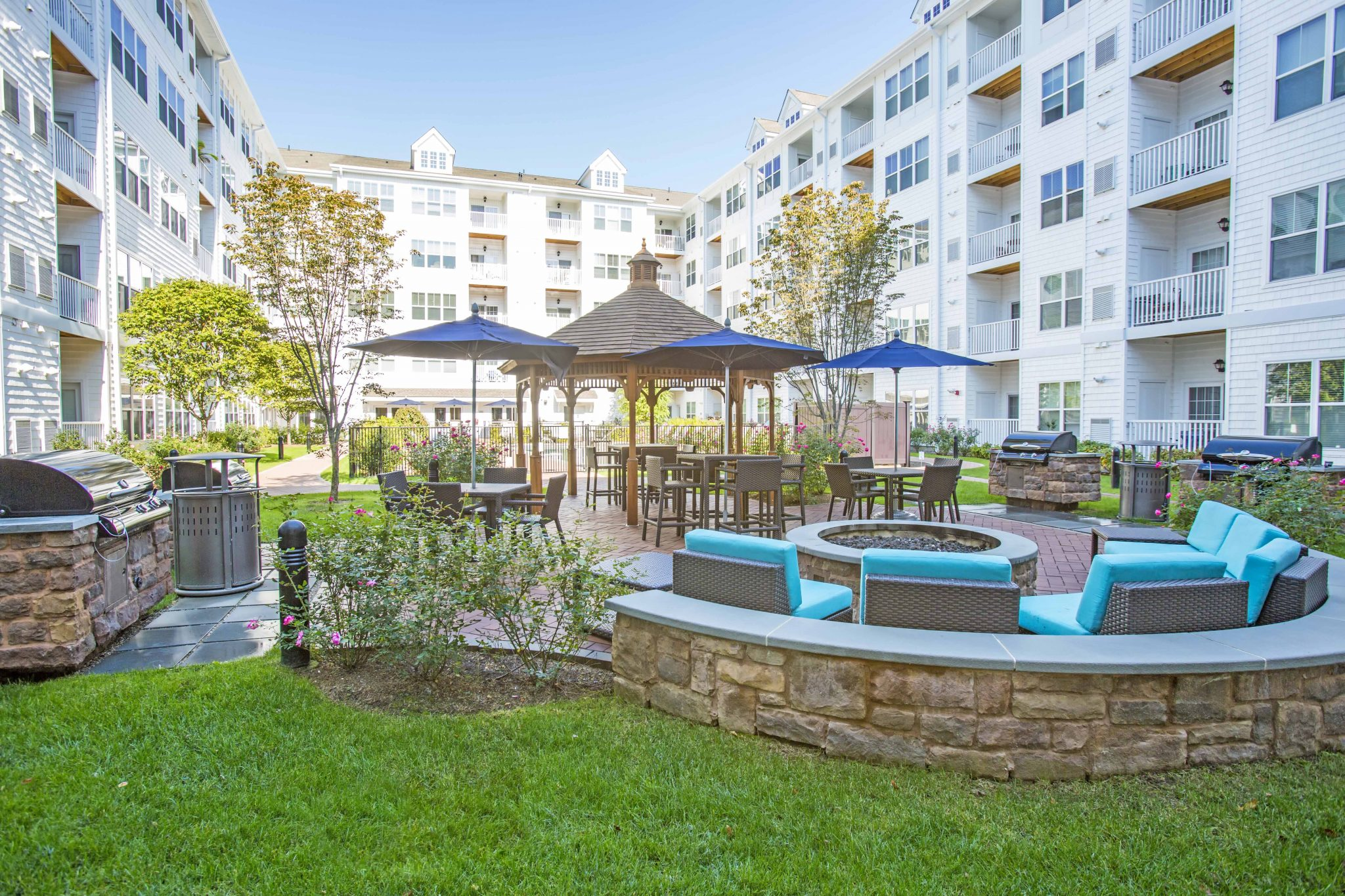 Exterior of courtyard between buildings with grass, seating around a fire pit, barbeques, and table seating.