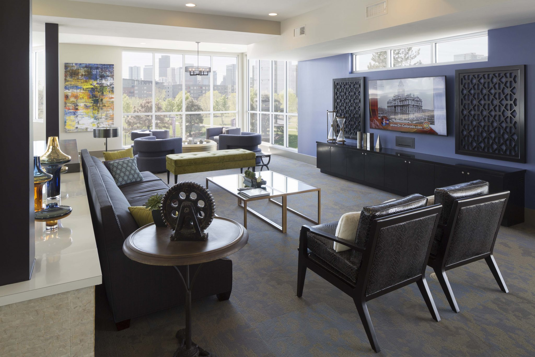 Interior of common area with couch, modern chairs and large-screen television.