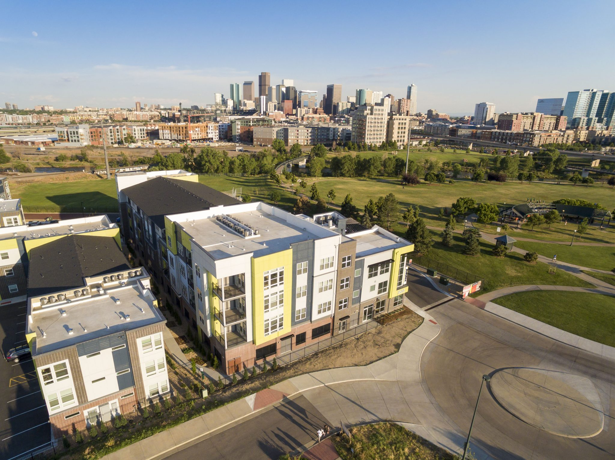 Aerial exterior of apartment complex with park and downtown skyline in background.