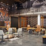 Interior of urban feeling common area with seating areas, high ceilings, and distressed wall graphic