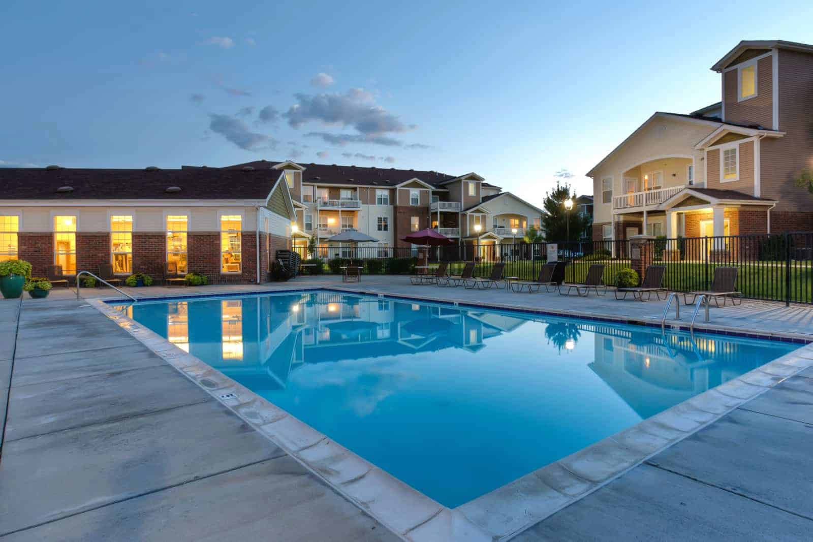 Exterior of swimming pool with apartment complex in background.
