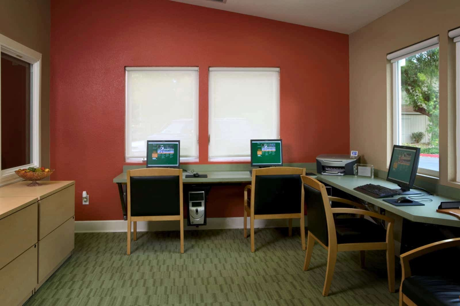 View of 3 computer stations and a printer in a business center.