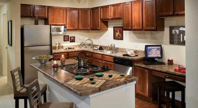 Interior of kitchen with stainless steel appliances and island.