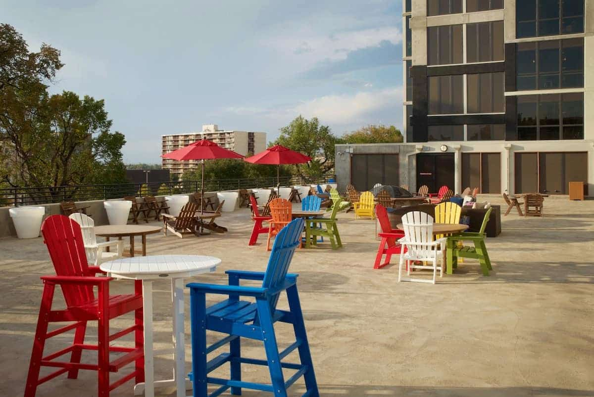 Roofdeck with adirondack chairs and barstools, tables, and umbrellas.