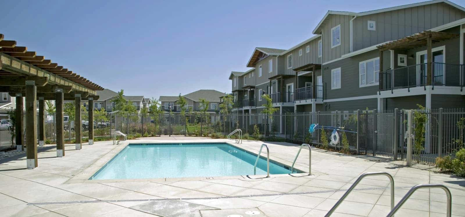 View of the pool area with the apartment buildings in the background.