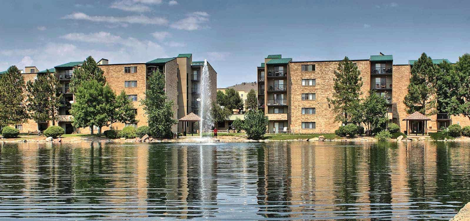 View of the lake and fountain with 5 story apartment buildings in the background.