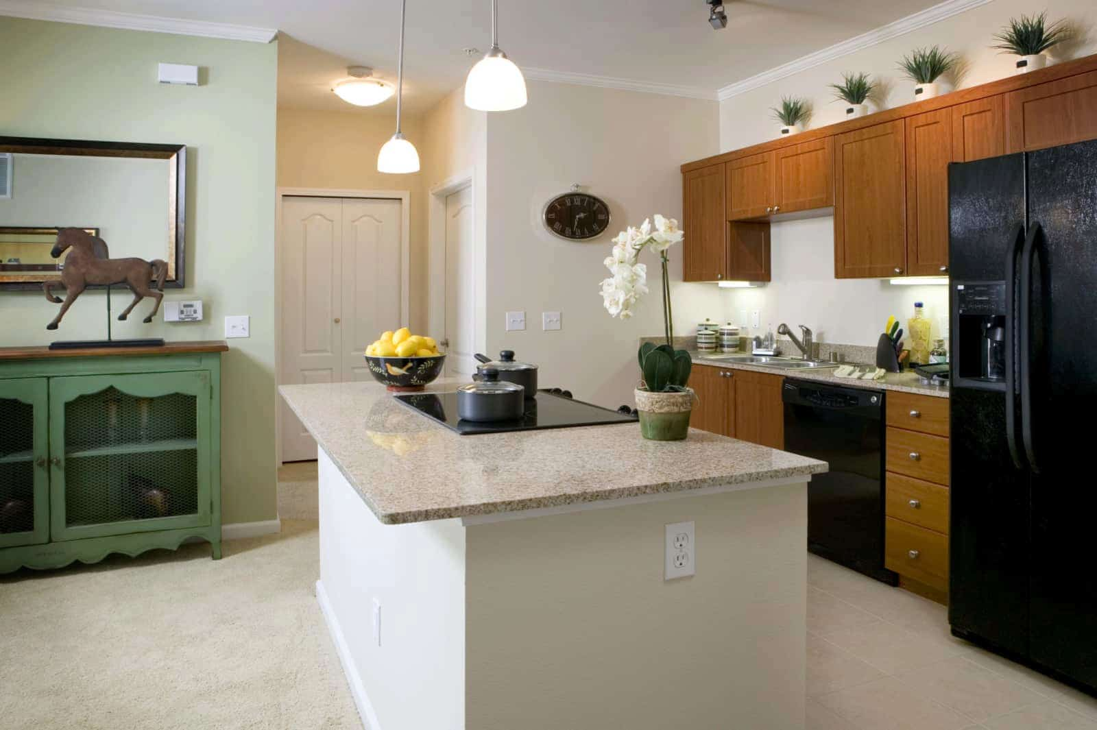 View of the kitchen with black appliances and granite countertop.