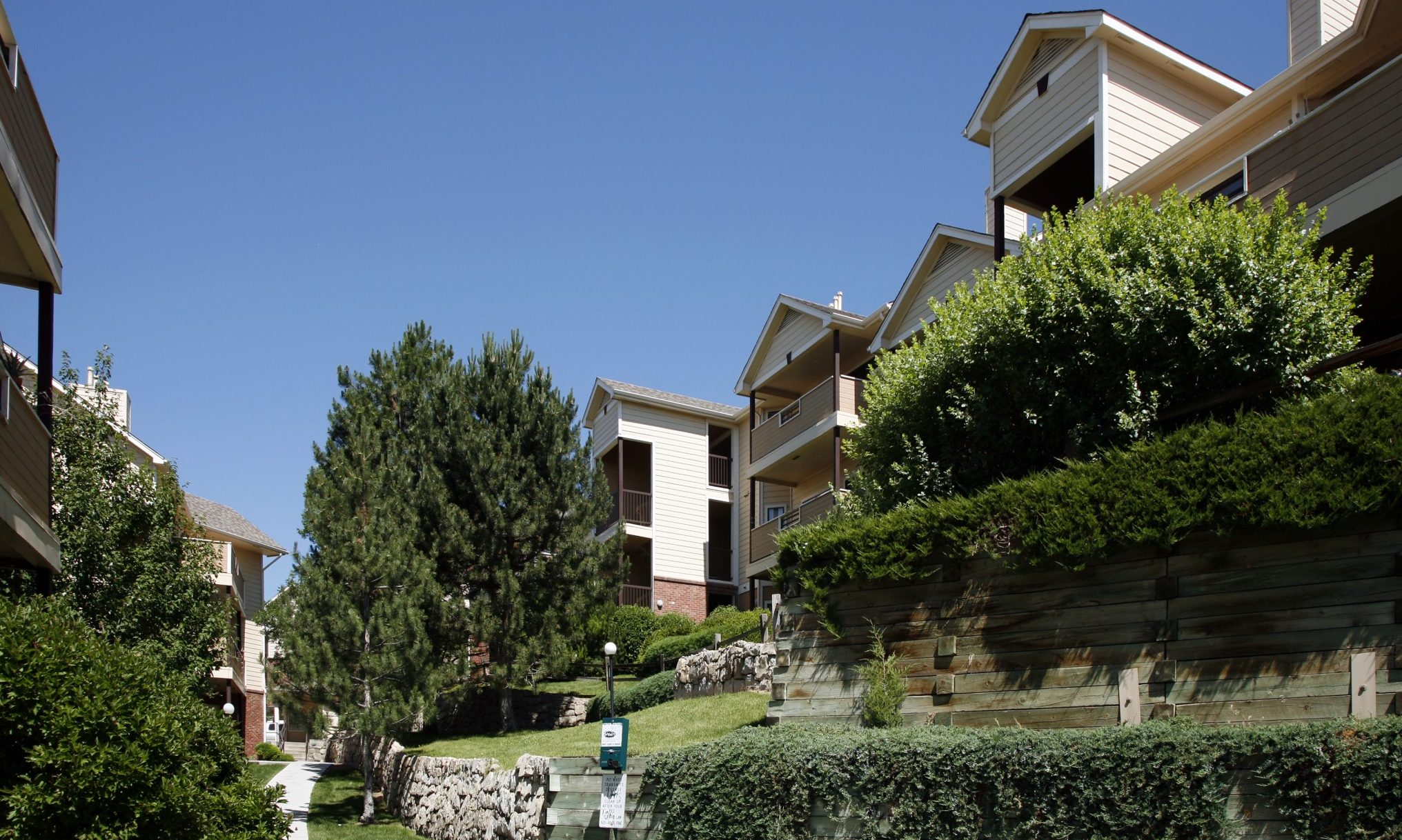 Upward view of apartment buildings and landscaping.