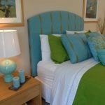 Close up of a bed and bedside table with a lamp, clock and candles on it.