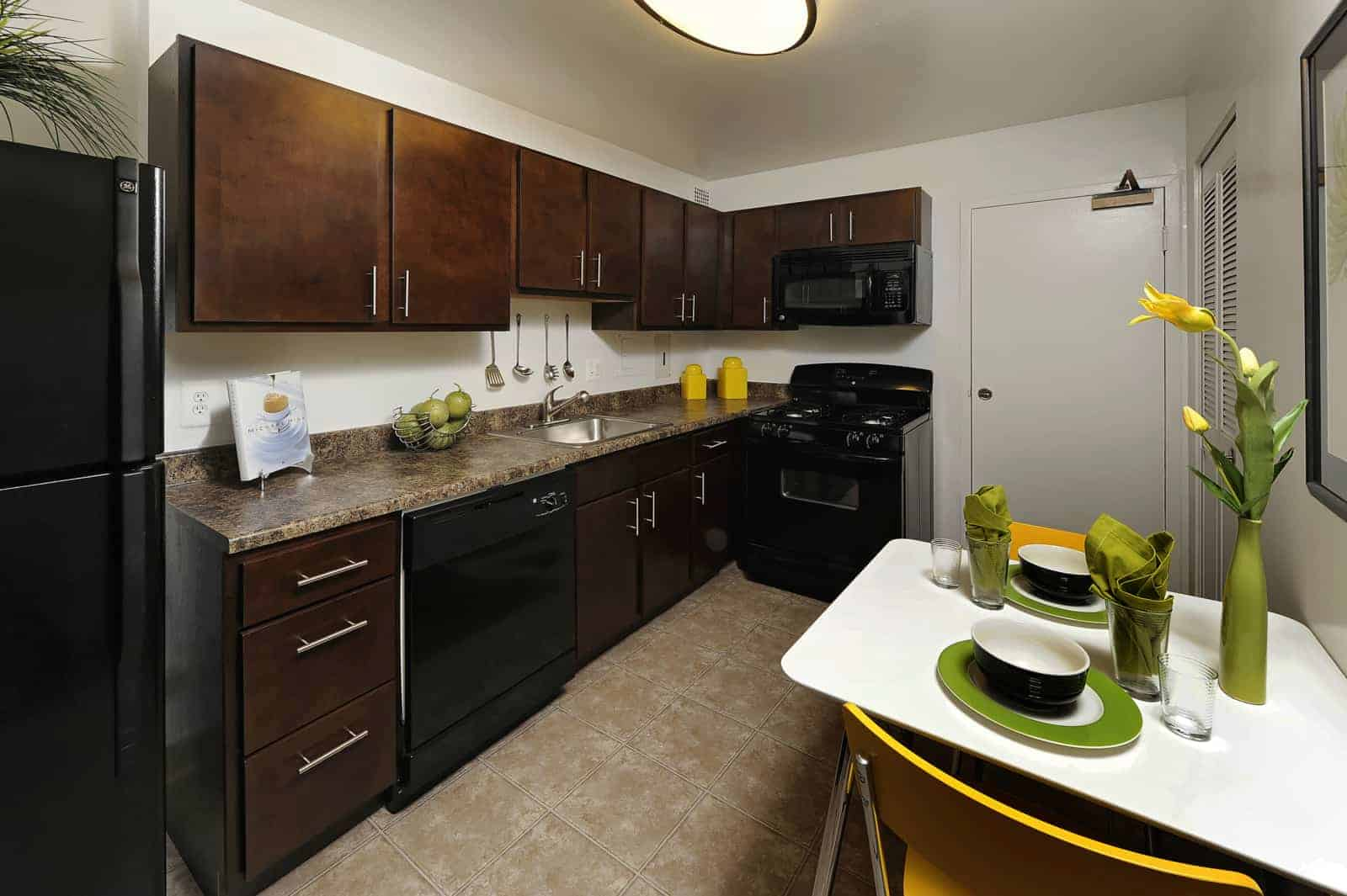 Interior of kitchen with black appliances and brown cabinets.