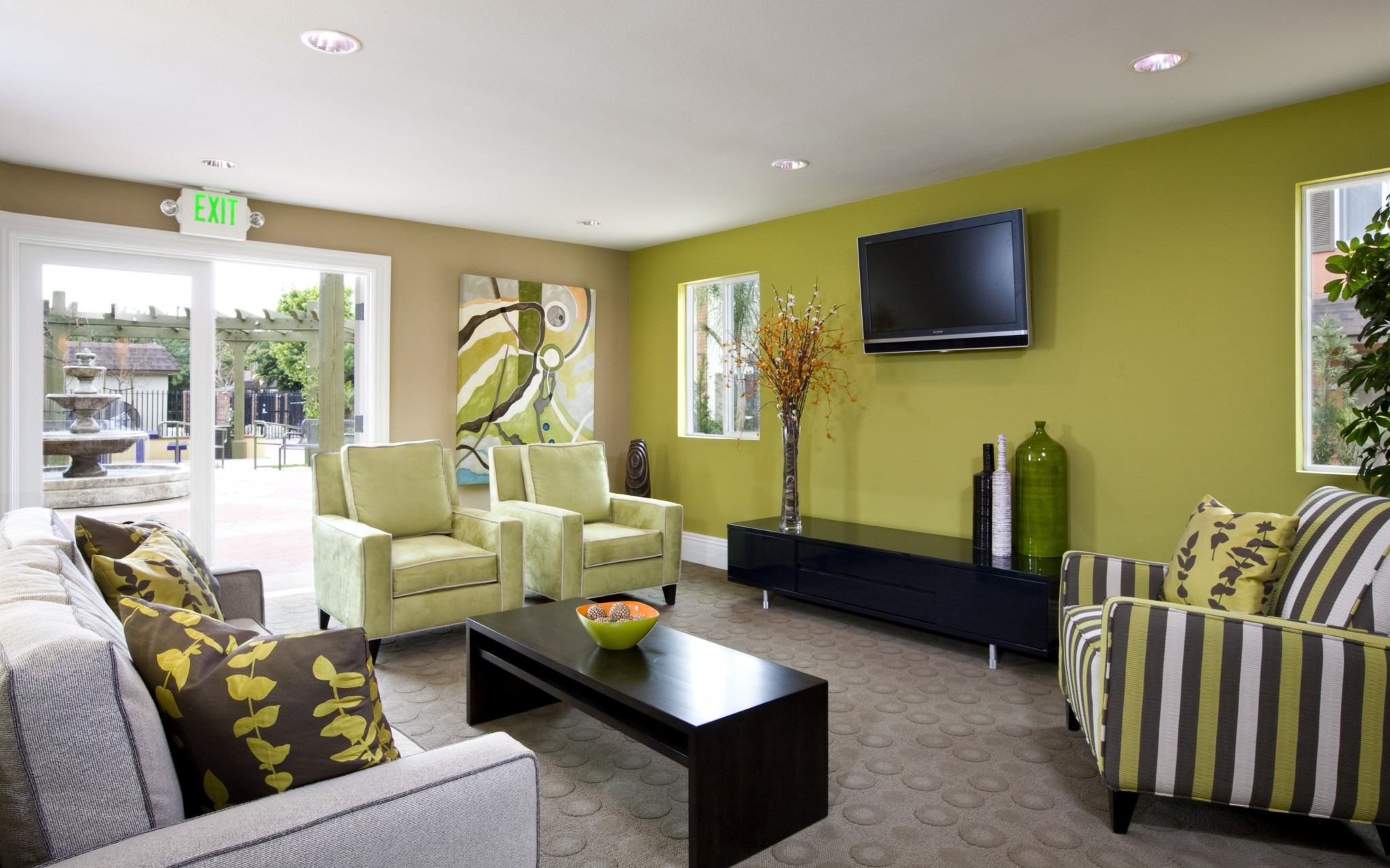 Interior of clubhouse with couch, chairs, coffee table, and TV.
