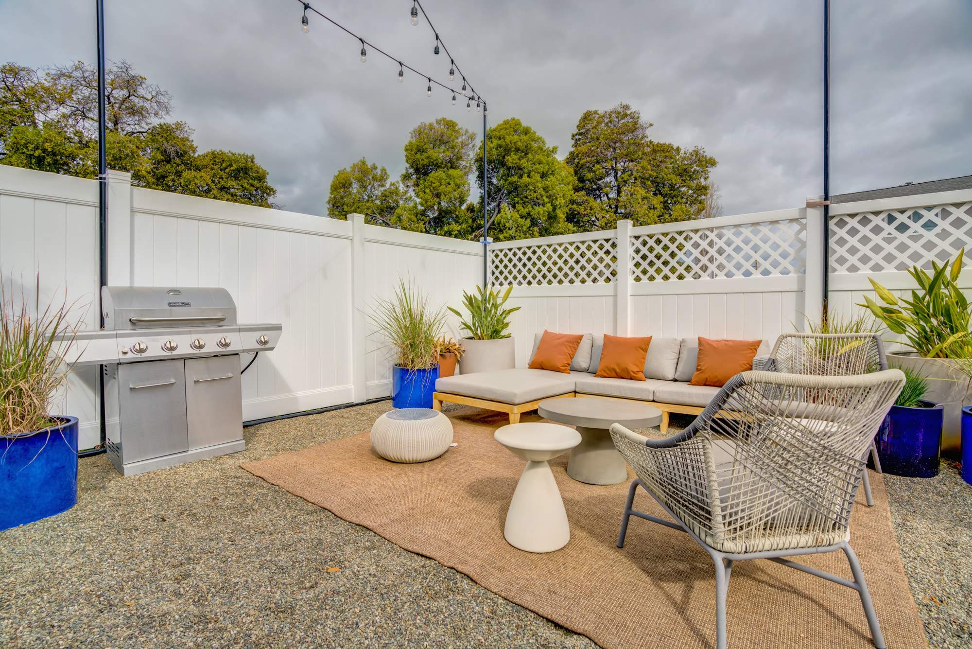 Apartment exterior sitting area with low couch, BBQ and latticed fence