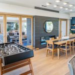 Interior with foosball table, large table and chairs, and fireplace with french doors to another room with couches