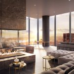 Interior of modern common area with couches, glass-enclosed fireplace, floor-to-ceiling windows with city views.