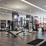 Interior of well appointed gym with city views through wall of windows